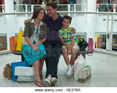 Smiling family in shopping mall relaxing on bench - Stock Photo