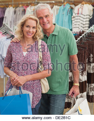 Couple carrying shopping bags in store - Stock Photo