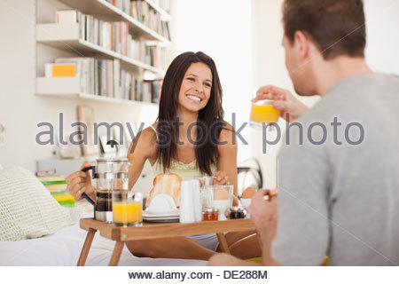 Couple eating breakfast in bed - Stock Photo