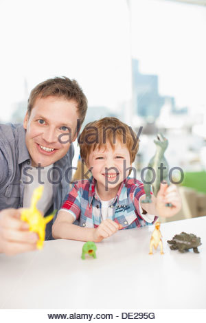 Father and son playing with plastic dinosaurs - Stock Photo