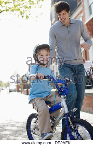 Father watching son ride bicycle on sidewalk - Stock Photo