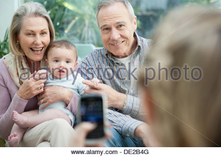 Smiling grandparents holding baby grandson and taking photograph on cell phone - Stock Photo