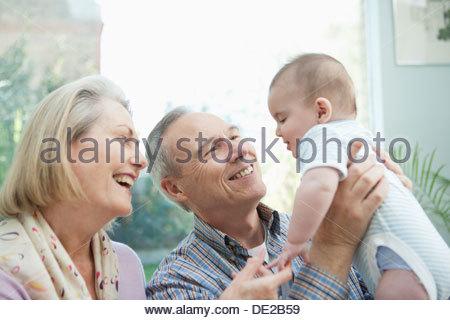 Smiling grandparents holding baby grandson - Stock Photo