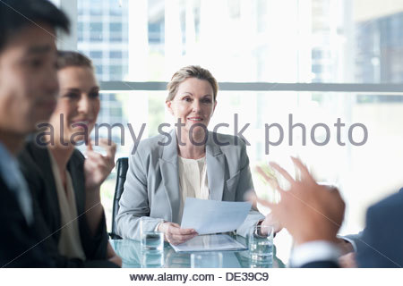 Smiling businesswoman leading meeting in conference room - Stock Photo