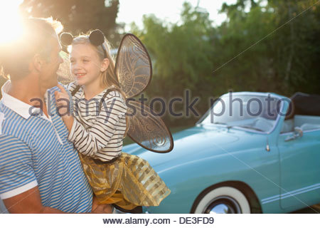 Father holding daughter in fairy wings - Stock Photo