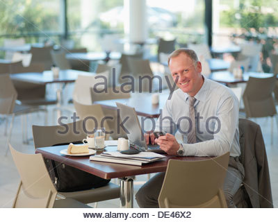 Businessman looking at cell phone in cafeteria - Stock Photo