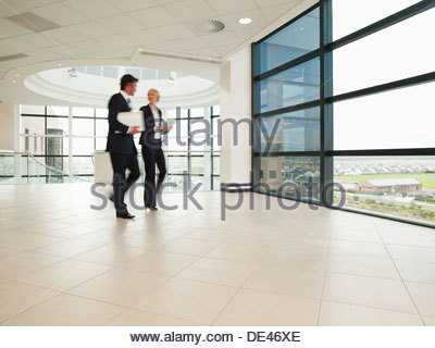 Business people walking through office lobby - Stock Photo