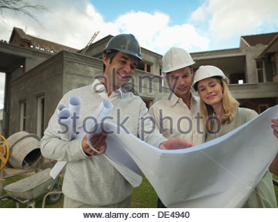 Architect and couple looking at blueprints outside house under construction - Stock Photo