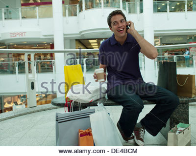 Smiling man in shopping mall talking on cell phone - Stock Photo
