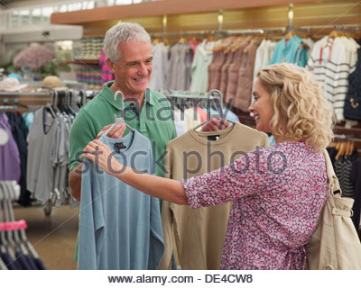 Couple shopping for clothing in store - Stock Photo