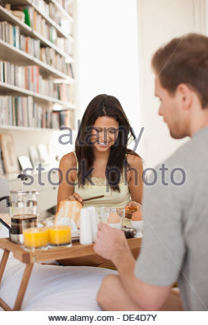 Man bringing wife breakfast in bed - Stock Photo