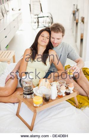 Happy couple having breakfast in bed - Stock Photo