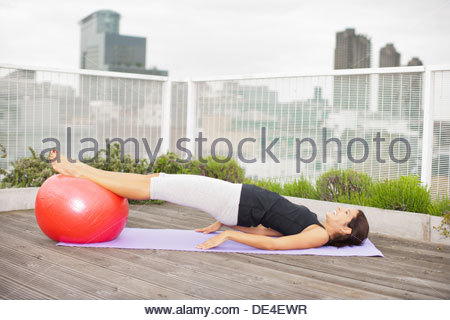 Woman exercising on rooftop deck - Stock Photo