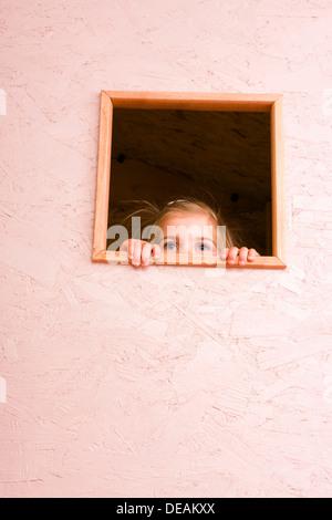 Girl, 3 years, looking through window - Stock Photo
