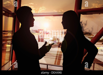 Two business people talking in the airport, Silhouette - Stock Photo