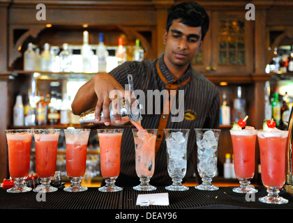 Bartender at Raffles hotel in Singapore making the famous Singapore sling cocktail drink - Stock Photo