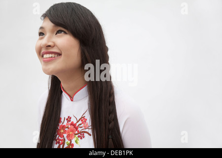 Portrait of smiling young woman with long hair wearing a traditional dress from Vietnam, studio shot - Stock Photo