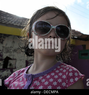 square portrait of six year old girl wearing sunglasses - Stockfoto