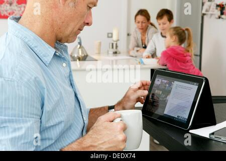 Man using tablet computer at home - Stock Photo