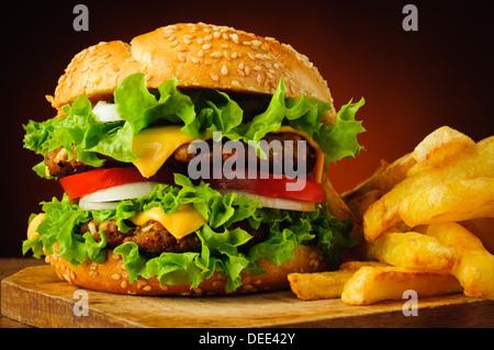 closeup of traditional cheeseburger or hamburger and frech fries - Stock Photo