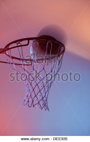 Basketball on rim of hoop - Stock Photo