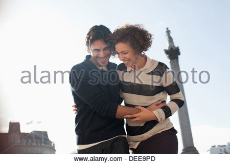 Couple hugging under monument in London - Stock Photo