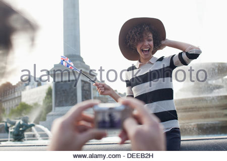 Man with digital camera taking photograph of happy woman with British flag in front of fountain - Stock Photo