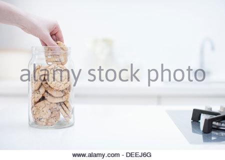 Hand reaching for cookie in jar - Stock Photo