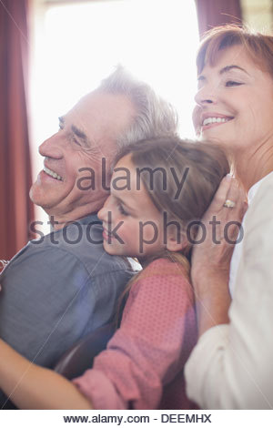 Happy grandparents and granddaughter hugging - Stock Photo