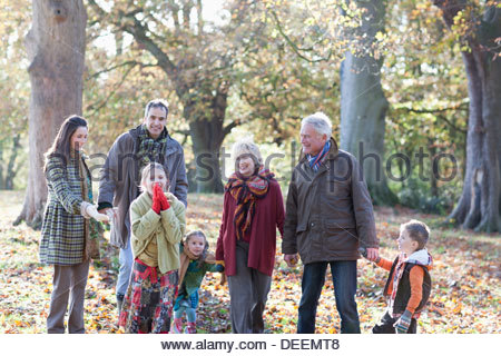 Extended family holding hands and walking in park - Stock Photo