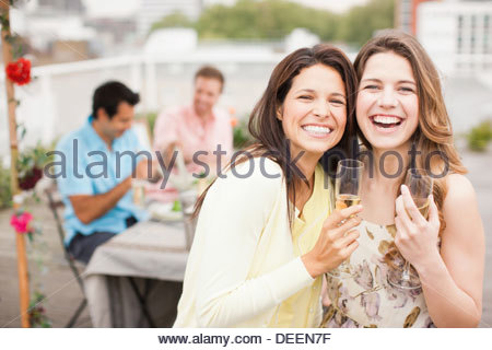 Laughing friends drinking Champagne at outdoor party - Stock Photo