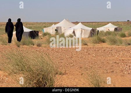 Two women from nomadic family, wearing the mulafa, Mauritanian traditional dress, walking back to their tented home - Stock Photo