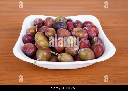 Acid purple and green Plums (Blackthorns) in bowl on wooden desk - Stock Photo