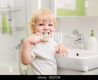 Happy kid brushing teeth - Stock Photo
