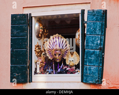 Venice Italy display window at souvenir store sells masks decorated clothing for fun and theater in ancient building - Stock Photo