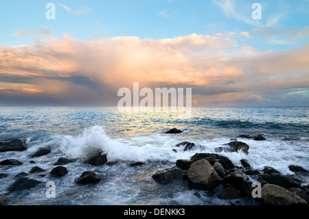 Rocky coast and sea waves at sunset - Stock Photo