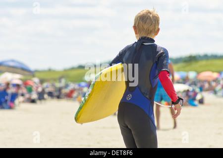 Surfer boy on sandy beach on sunny day - Stock Photo