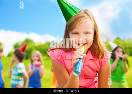 Portrait of happy girl with noisemaker whistle on a birthday party wearing cap with friends standing on background - Stock Photo