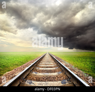Railway in the field and storm clouds - Stock Photo