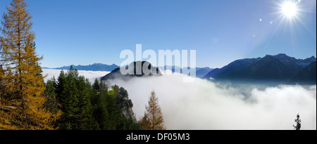 View from the ruins of Falkenstein Castle over the mist-covered Vilser Tal or Vils Valley and Zwoelferkogel mountain - Stock Photo