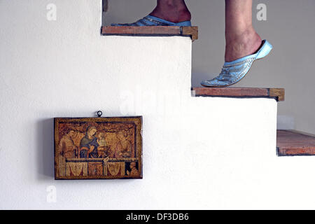 Female feet of a woman wearing traditional maroccan Babush and climbing up the stairs with a picture of a bible - Stock Photo