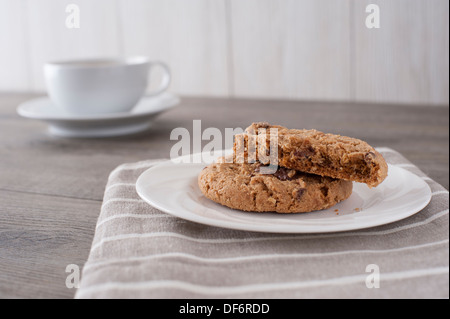 A white china plate containing a home baked cookie  laying on a linen cloth with a coffee cup and saucer in the - Stock Photo