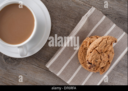 Viewing down onto a white bone china cup and saucer containing white coffee with a home baked choc chip cookie on - Stock Photo