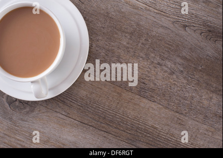 white bone china cup and saucer containing a refreshing  white coffee resting on a distressed wooden background - Stock Photo
