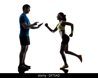 one woman exercising jogging with man coach using digital tablet in silhouette on white background - Stock Photo