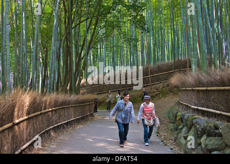 People walking through a bamboo forest in the Sagano area of Kyoto. - Stock Photo