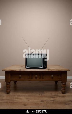 An old retro TV on a table with blank screen in an empty room - Stock Photo