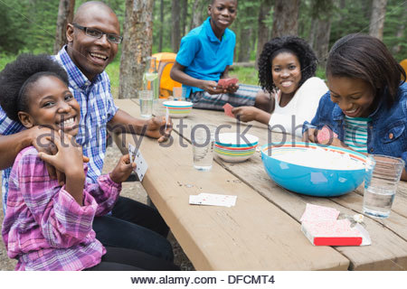 Family of five playing cards at campground - Stock Photo