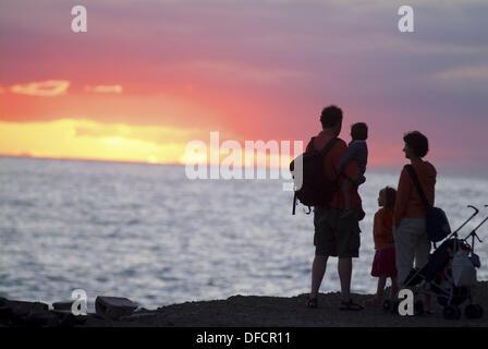 Family on beach at sunset - Stock Photo