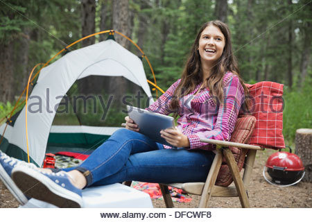 Happy teenage girl with digital tablet sitting at campsite - Stock Photo